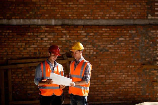 Architect en bouwmanager gekleed in oranje werkvesten en helmen bespreken documentatie op een bakstenen muurachtergrond.