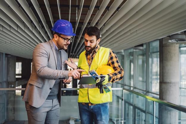 Architect en bouwvakker permanent in het bouwen van bouwproces en blauwdrukken op tablet kijken