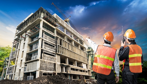 Architect en voorman in de handeling van controlearbeider van draagbare radio bij bouwwerf