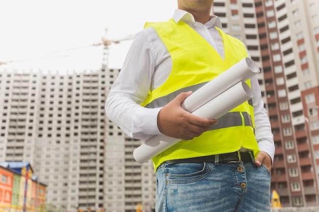 Architect in veiligheidsvest poserend met blauwdrukken bij nieuwbouw