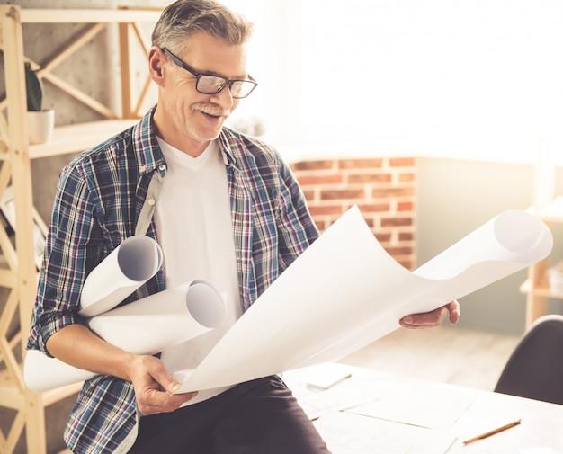 Architect in vrijetijdskleding en bril bestudeert tocht.