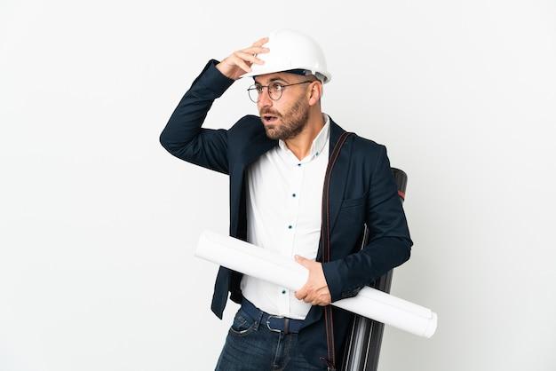 Architect man met helm en blauwdrukken geïsoleerd op een witte muur te houden die verrassingsgebaar doet terwijl hij naar de zijkant kijkt