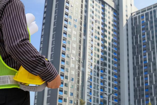 Architect met gele beschermende helm bij groot condominium bouwterrein