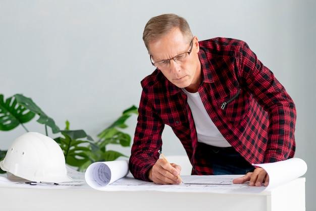 Architect met glazen die aan project werken