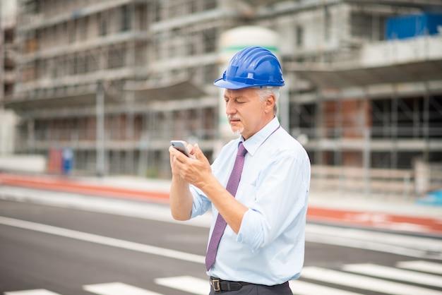 Architect met zijn mobiele smartphone voor een bouwplaats