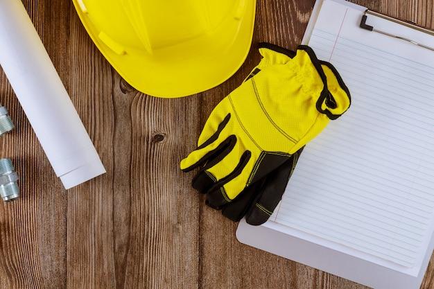 Architect of ingenieur bezig met blauwdruk architectuur modus in kantoorconstructie beschermende handschoenen op gele veiligheidshelm
