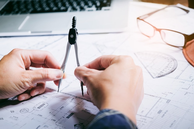 Architect of ingenieur die in bureau aan blauwdruk werken