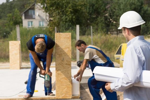 Architect of ingenieur op een bouwplaats, kijkend naar arbeiders die geprefabriceerde wandpanelen monteren op een nieuwbouwhuis