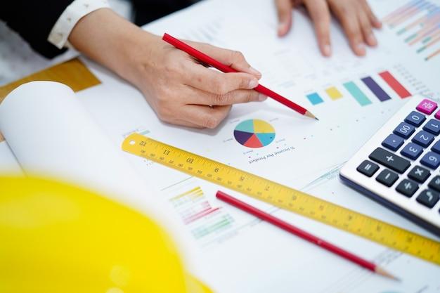 Architect of ingenieur werken projectboekhouding met grafiek.