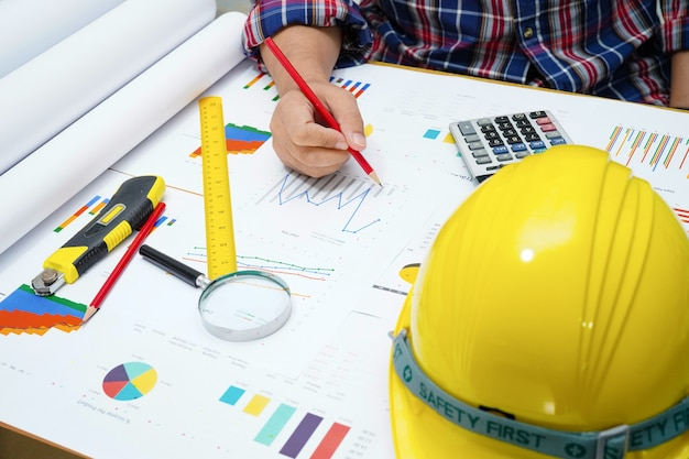 Architect of ingenieur werkend projectboekhouding met grafiek in bureau.