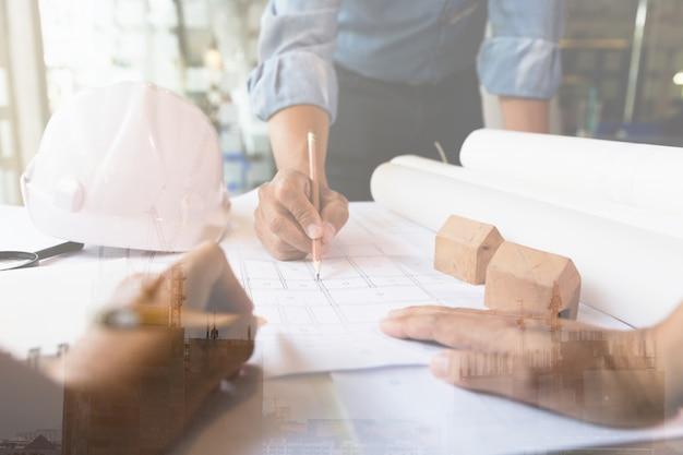Architect of ingenieursvergadering, die met blauwdrukken in bureau, bouwconcept werken. dubbele belichting met kraan en gebouw in aanbouw