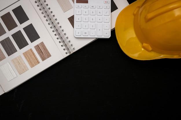 Architect ontwierp het gebouw in het ontwerpbureau, de plattegrond met catalogi decoratieve materialen en andere accessoires op de zwarte houten tafel.