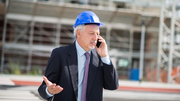 Architect praten aan de telefoon voor de bouwplaats