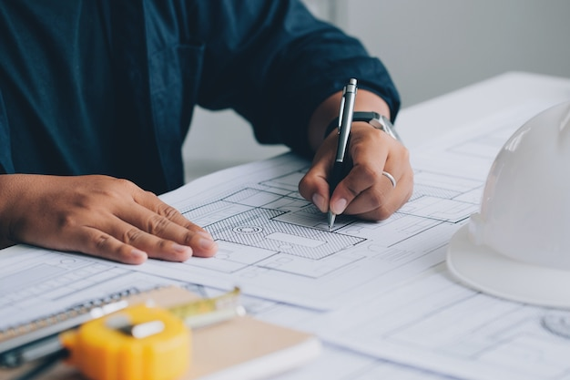 Architect tekenen op een blauwdruk op architectonisch project op de bouwplaats op kantoor