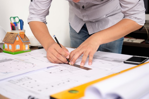 Architect tekent bouwplannen op blauwdrukpapier met potlood.