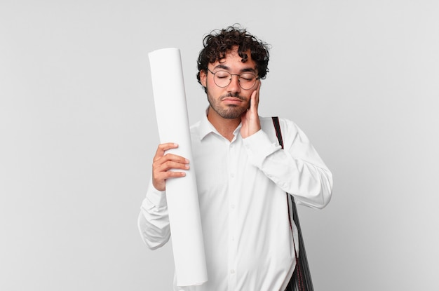 Architect voelt zich verveeld, gefrustreerd en slaperig na een vermoeiende, saaie en vervelende taak, terwijl hij zijn gezicht met de hand vasthoudt