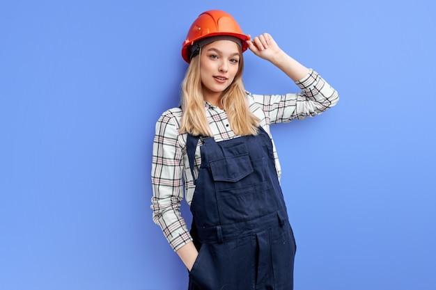 Architect vrouw in overall geïsoleerd op blauwe studio achtergrond, jonge blanke dame in oranje helm poseren