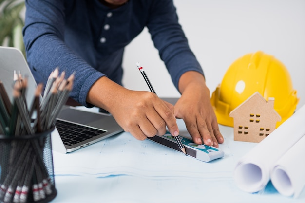 Architect werkt en planning op blauwdruk, engineering objecten op de werkplek met laptop