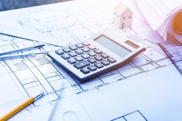 Architect werkt met rekenmachine aan planontwerp
