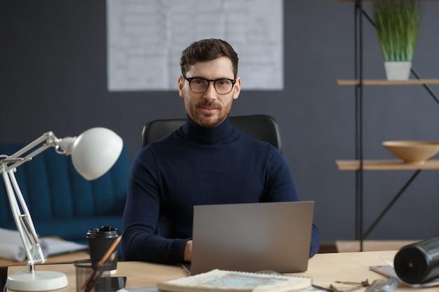 Architect werkt op kantoor met laptop zakelijk portret van knappe bebaarde man met bril...