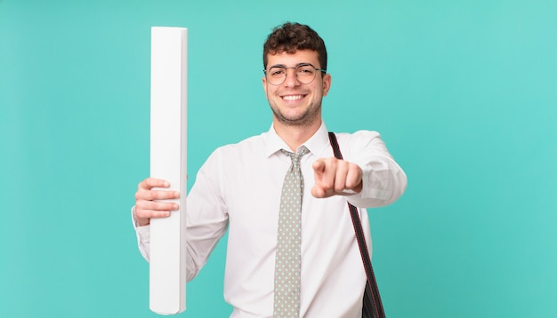 Architect wijzend op de camera met een tevreden, zelfverzekerde, vriendelijke glimlach, jou kiezen