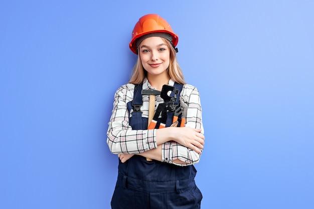 Architect zakenvrouw in oranje helm staande tegen blauwe muur, jonge blanke vrouw in overall uniform werk als constructeur ingenieur