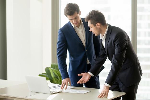 Architecten die de tekeningen van het bouwplan bespreken