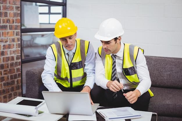 Architecten die op laptop werken