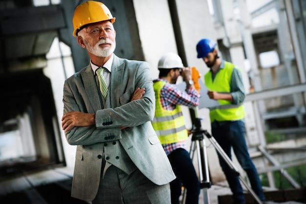 Architecten en bouwingenieur of landmeter discussieplannen en blauwdrukken