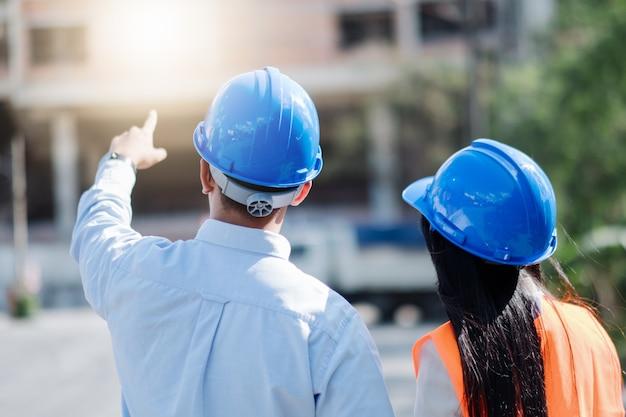 Architecten en ingenieur op een bouwplaats kijken naar blauwdrukken en wijzen.