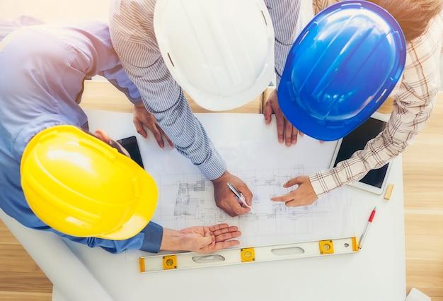 Architecten en ingenieurs komen bijeen en plannen gezamenlijke actie met commitment. afbeelding bovenaanzicht.
