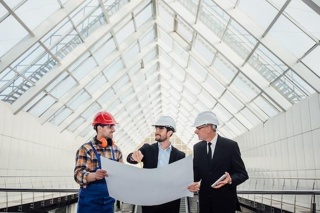 Architecten en voorman bespreken het ontwerp van het project