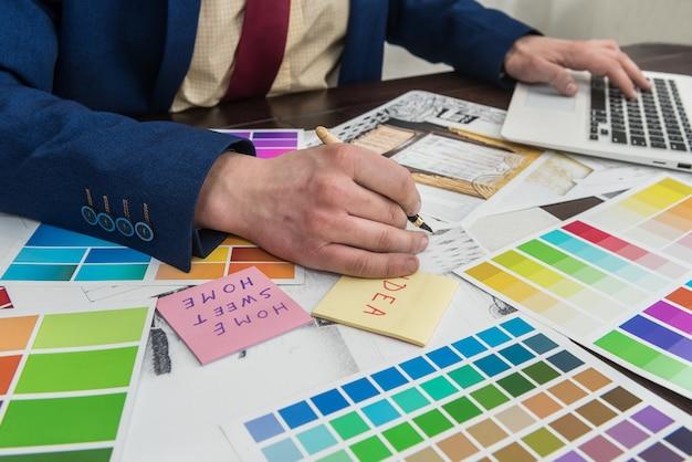 Architecten handen tekening van moderne appartementen met kleurstaal en laptop op creatief bureau, kantoor. man kleuren kiezen voor kamerdecoratie