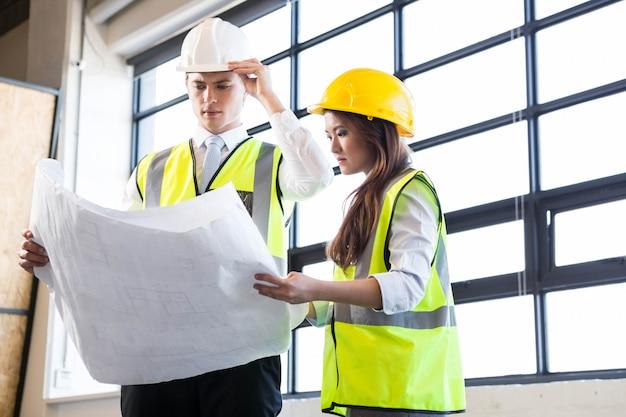 Architecten kijken naar blauwdruk in kantoor