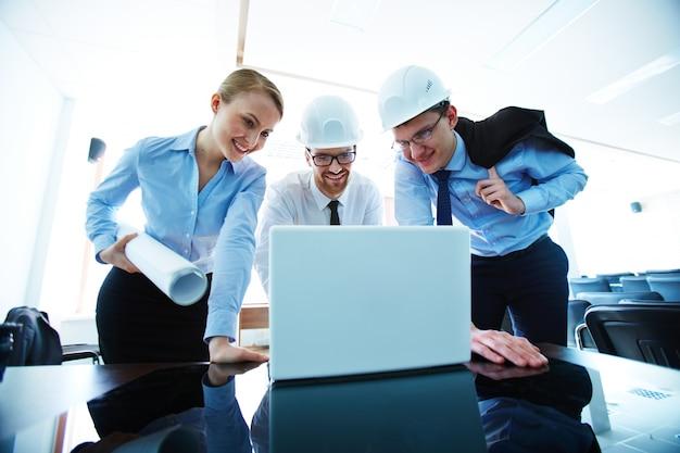 Architecten kijken naar laptop scherm