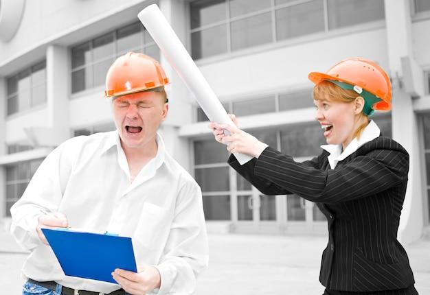 Architecten man en vrouw kick roll op hoofd chef