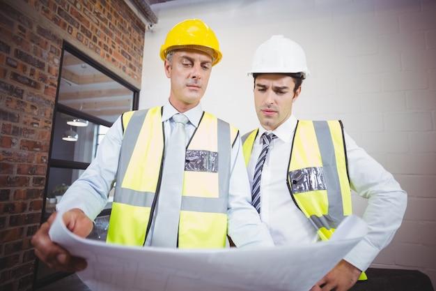 Architecten werken terwijl ze blauwdruk vasthouden