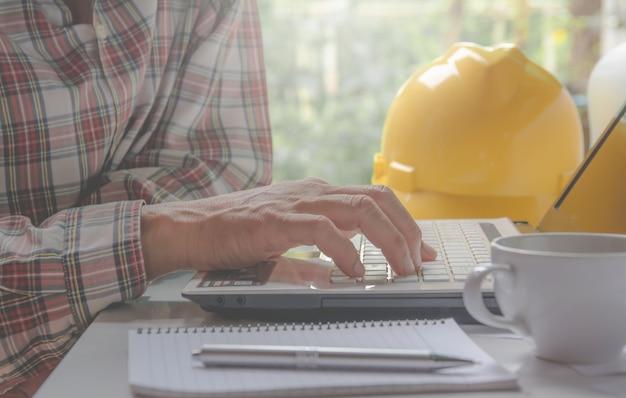 Architectenieur die laptop voor het werken met gele helm met behulp van