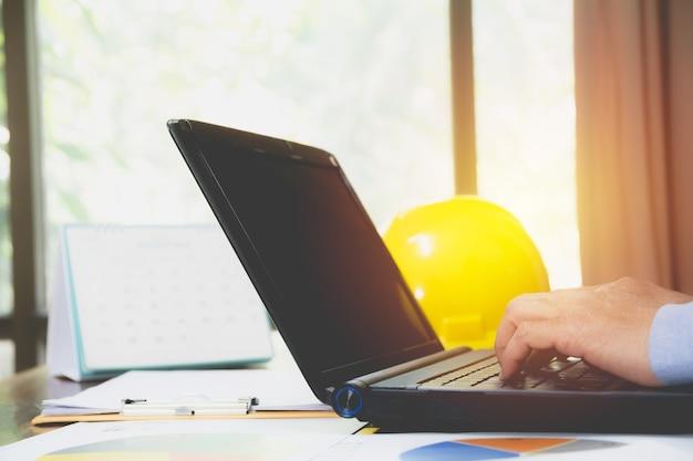 Architectenieur die laptop voor het werken met gele helm op bureau met behulp van.