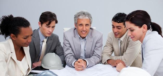 Architectenmanager in een ontmoeting met zijn team om plannen te bestuderen