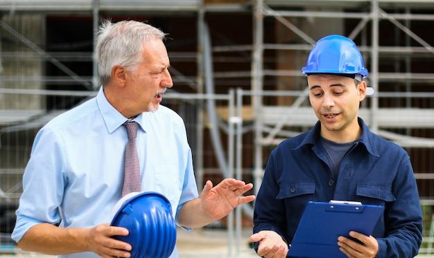 Architectenontwikkelaars beoordelen bouwplannen op bouwplaats