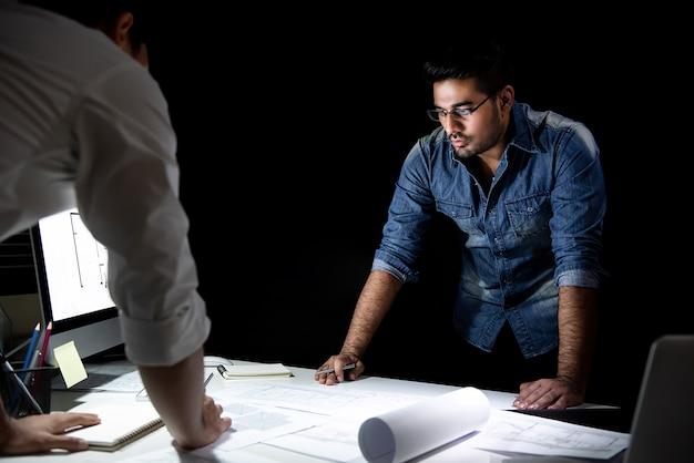 Architectenteam die project bespreken bij nacht