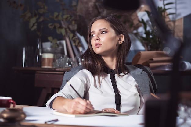 Architectenvrouw die aan tekentafel in kantoor werkt
