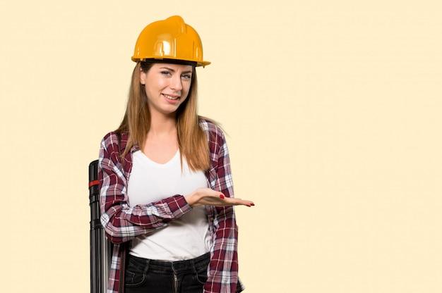 Architectenvrouw die een idee voorstellen terwijl het kijken naar glimlachend op geel