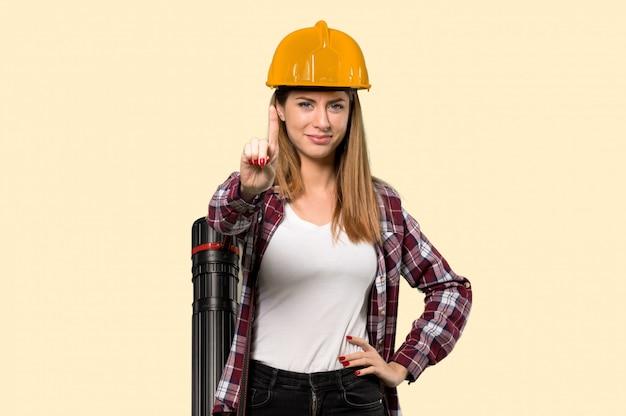 Architectenvrouw die en een vinger over geïsoleerde gele muur tonen opheffen