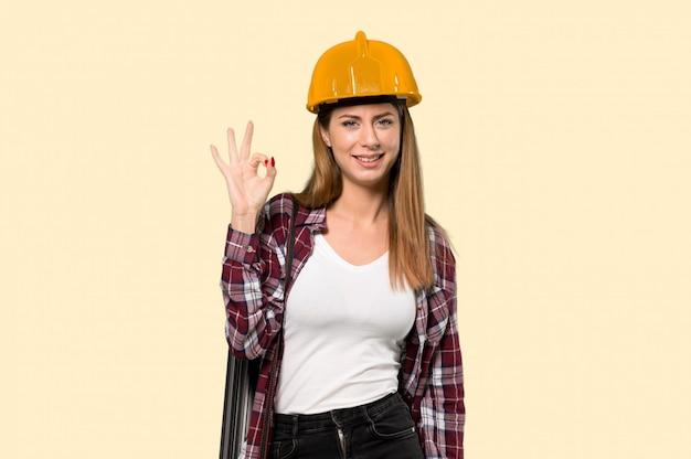 Architectenvrouw die ok teken met vingers over geïsoleerde gele muur tonen