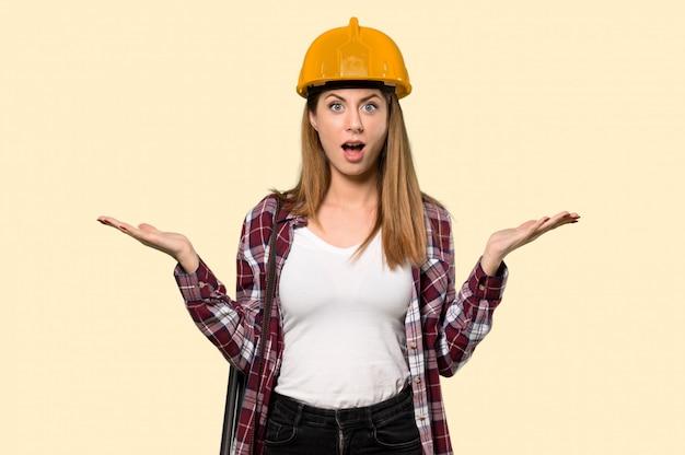 Architectenvrouw met geschokte gelaatsuitdrukking op geel