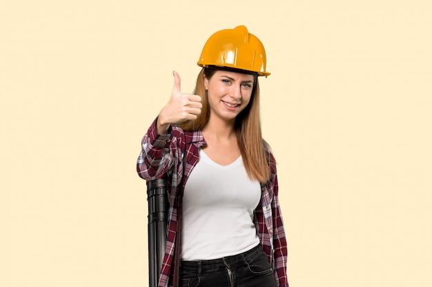Architectenvrouw met omhoog duimen omdat iets goeds is gebeurd over geïsoleerde gele muur