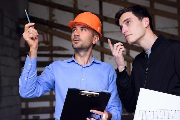 Architectingenieur die oranje helm draagt op de werkende plaats die de projectplannen verklaart aan de klant