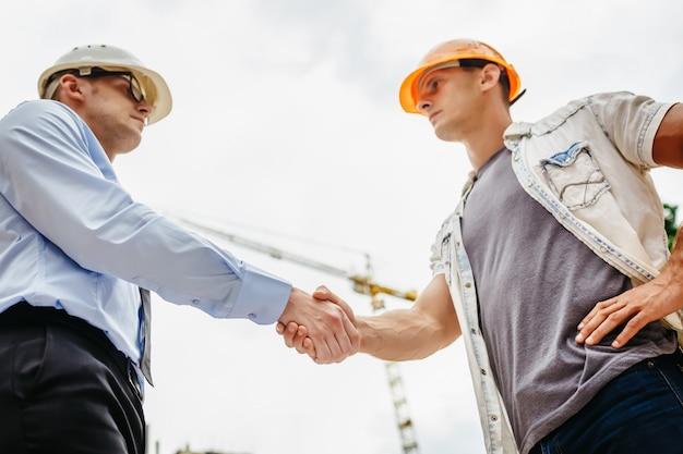 Architectingenieur het schudden overhandigt andere hand bij bouwwerf. zakelijk teamwork, samenwerking, succes samenwerkingsconcept